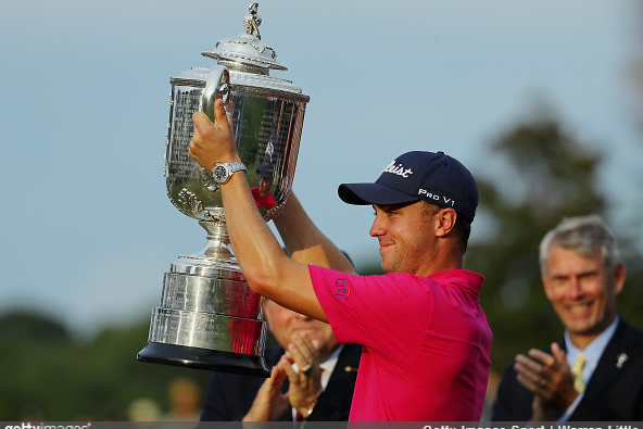 Justin Thomas holds up the trophy.
